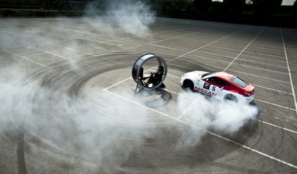 Nissan 370Z doing donuts around a Sony Playstation gaming pod