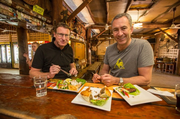 Territory Mates Mark Skaife and Mark Beretta tuck into a territory style banquet including Buffalo and Barra at the Annaburoo Bark Hut Inn on the Kakadu Highway.