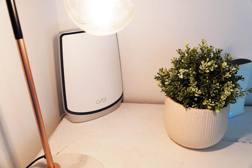 Netgear Orbi WiFi 6  under a light next to a pot plant