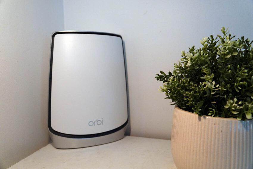 Netgear Orbi WiFi 6 sitting next to a pot plant