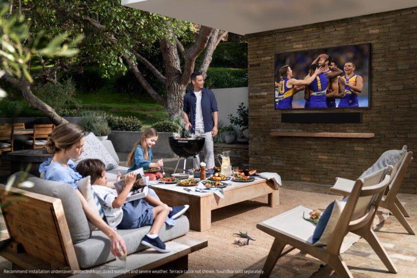 A family enjoys the footy on their Samsung Terrace outdoor TV