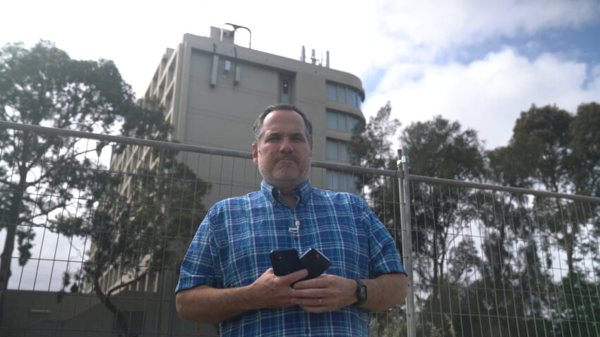 Trevor Long standing in front of a building with 5G antennas on it.