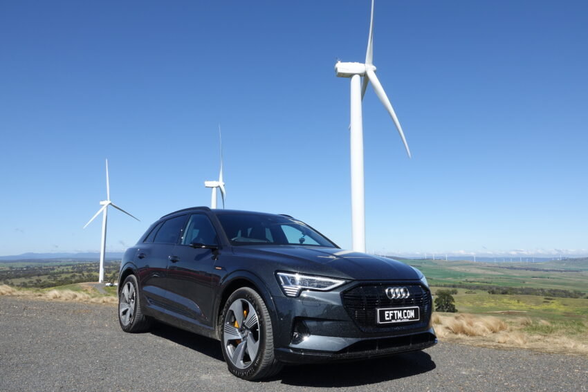 An Audi e-tron in grey, parked in front of huge wind turbines
