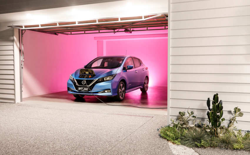 Nissan Leaf e+ in a garage lit up in pink light