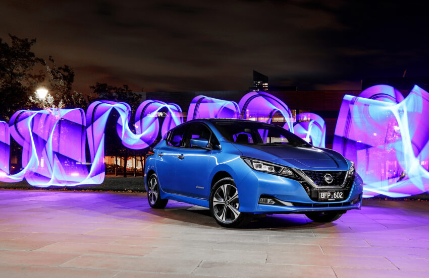 Nissan Leaf e+ at night with a bright colour display behind it